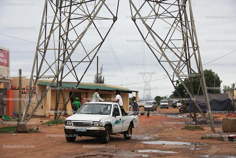 Carros passando pelo meio das torres da energia eléctrica