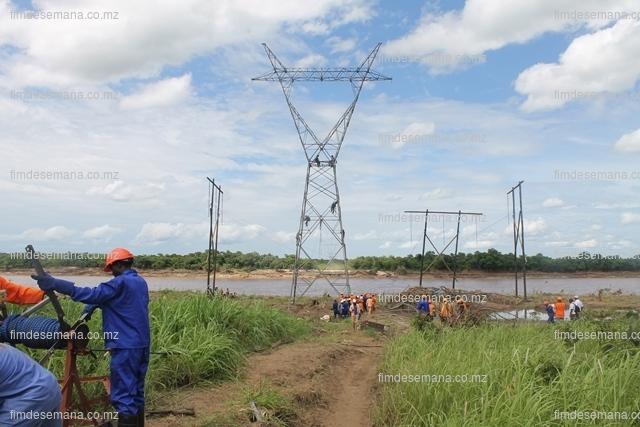 Técnicos da EDM durante montagem da linha no rio Licungo