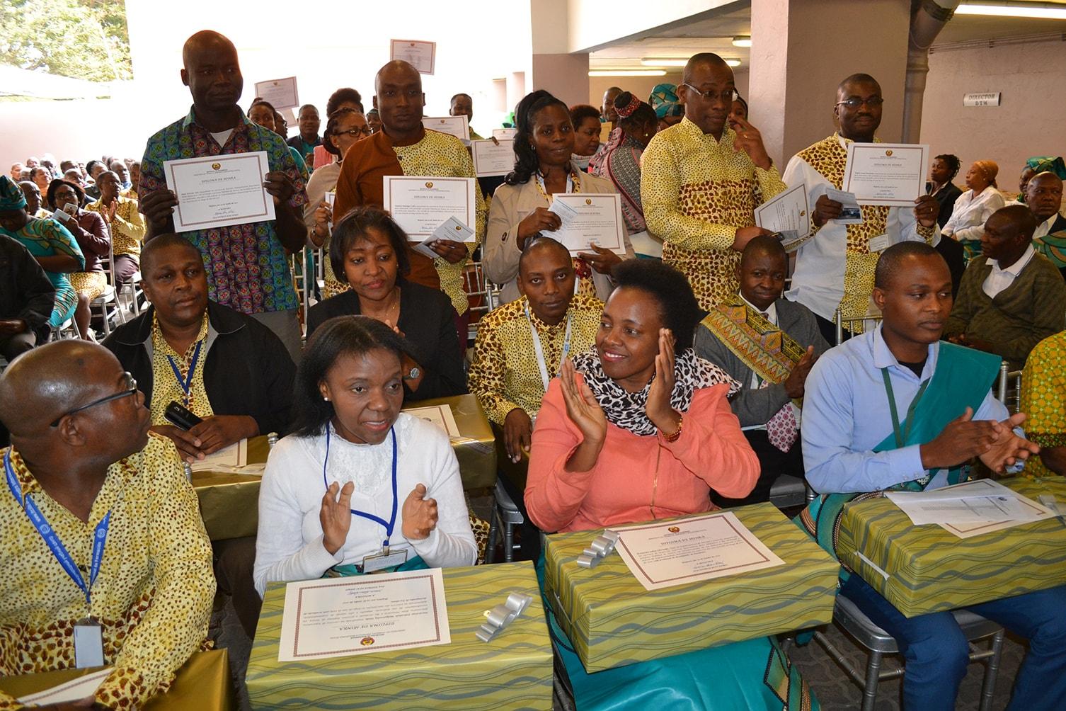 Funcionários premiados exibindo seus diplomas