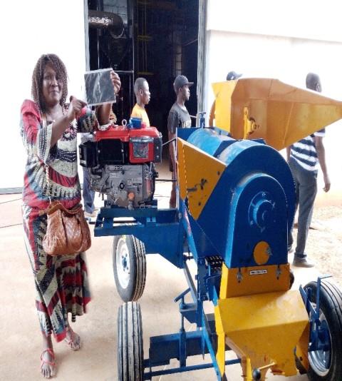 A beneficiária Amélia Bitone exibindo a sua máquina debulhadora